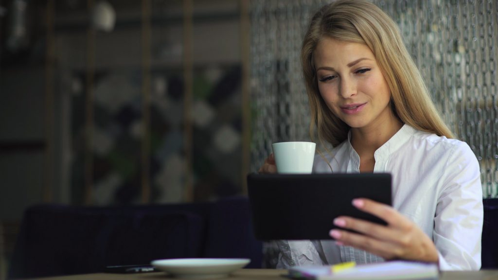 Lady looking at ipad with coffee