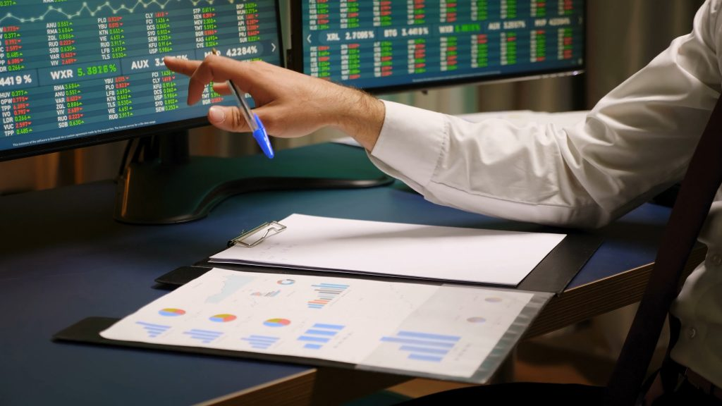 Hand looking at computer screen of stocks