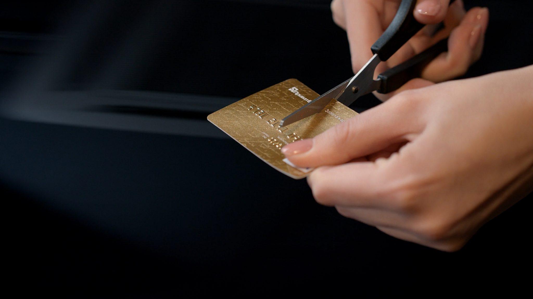 Hands cutting credit card