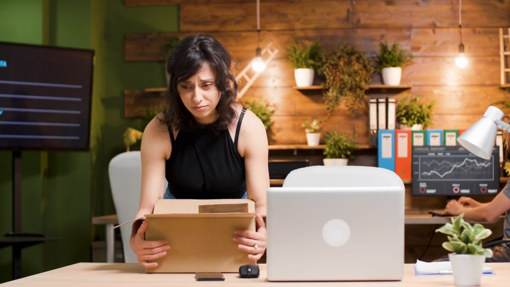 Laid off woman packs boxes in office