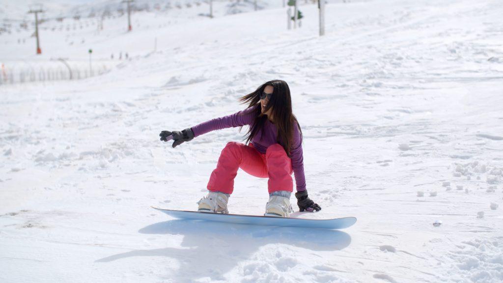 Girl falling on snowboard