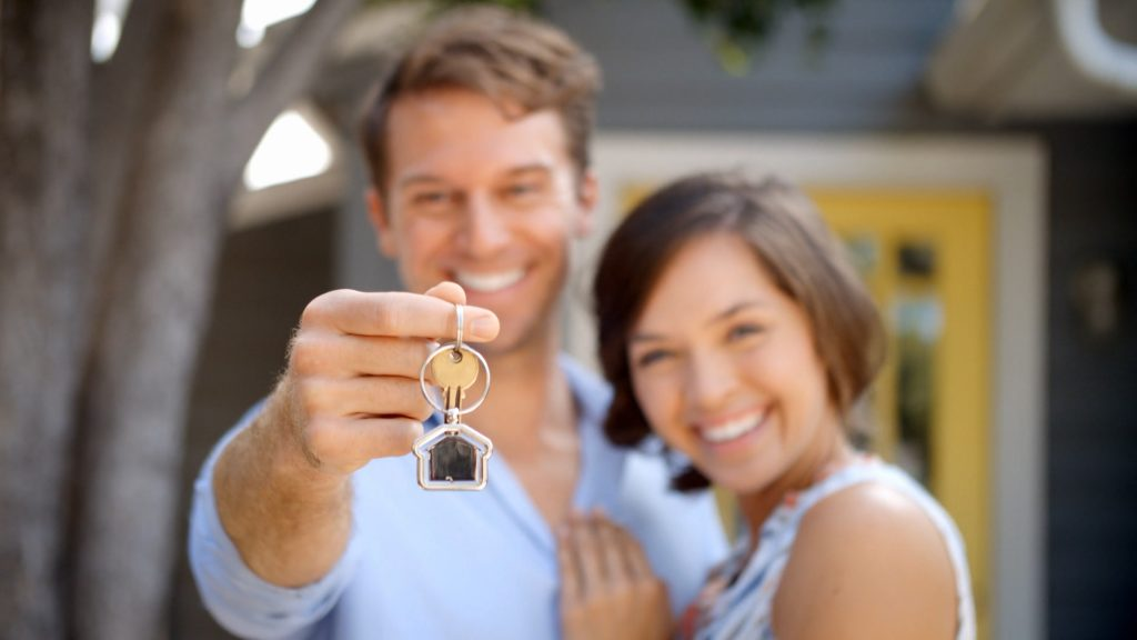 Couple holding up keys to new house