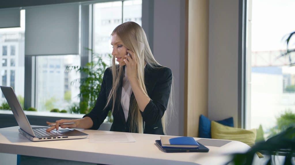 Woman on desk speaking on phone