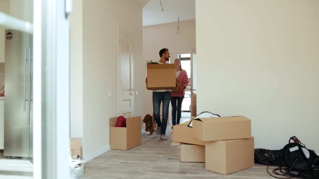 Man walking into new house with boxes