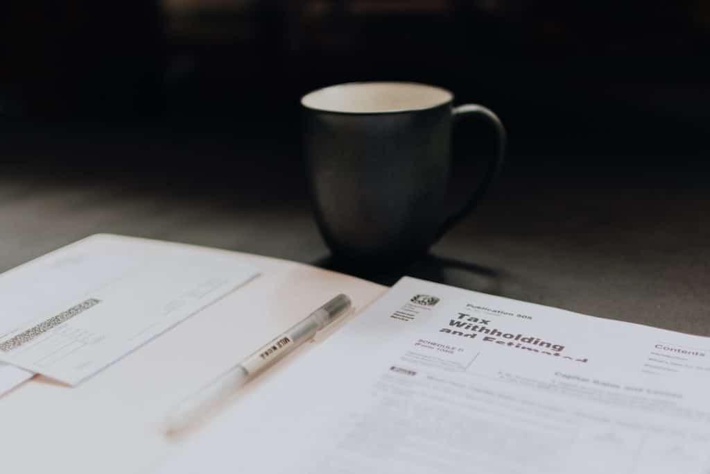 Tax files on table with coffee cup